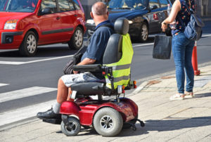 Man crossing the street in an electric wheelchair