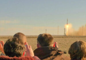 A group of people watching and photographing the launch of the spacecraft