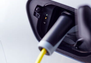 Close Up Of Power Cable Charging Environmentally Friendly Zero Emission Electric Car In Garage